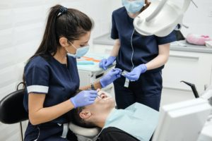 female dentist with assistant curing teeth of patient